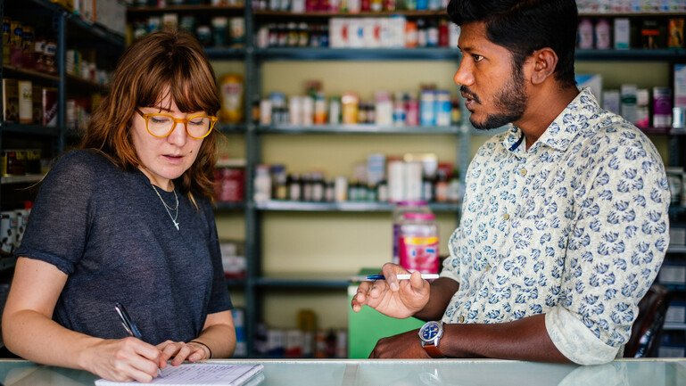 A pharmacist talking and a researcher taking notes in a pharmacy in Bangalore, India.