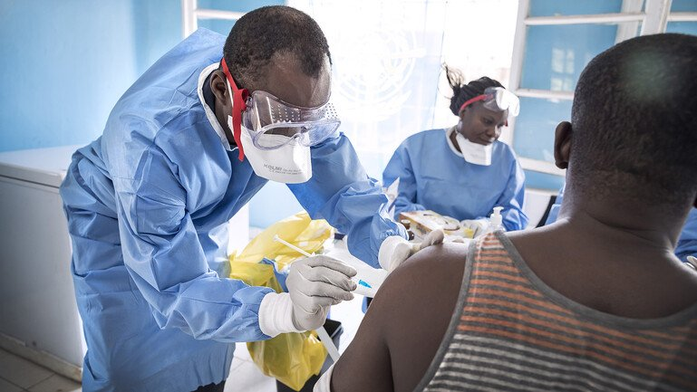 Doctor vaccinates a patient in the company of a nurse.