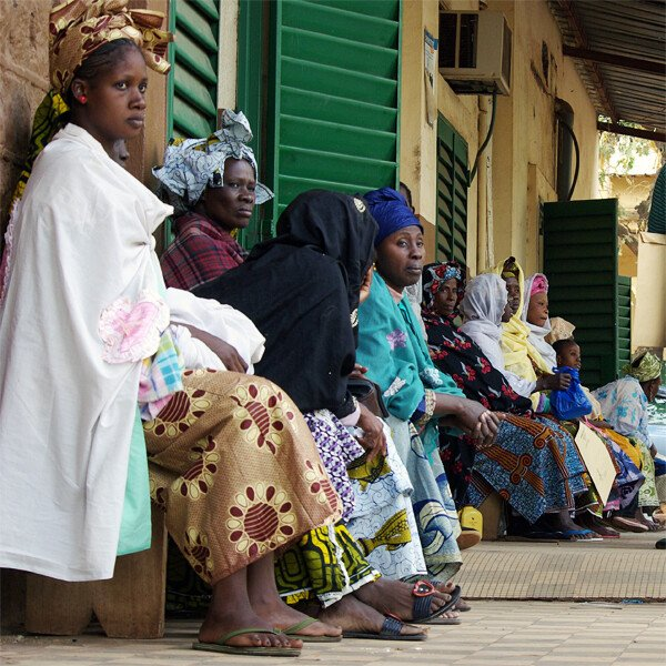 Women in brightly coloured clothing are sitting in the queue at a hospital in Bamako.
