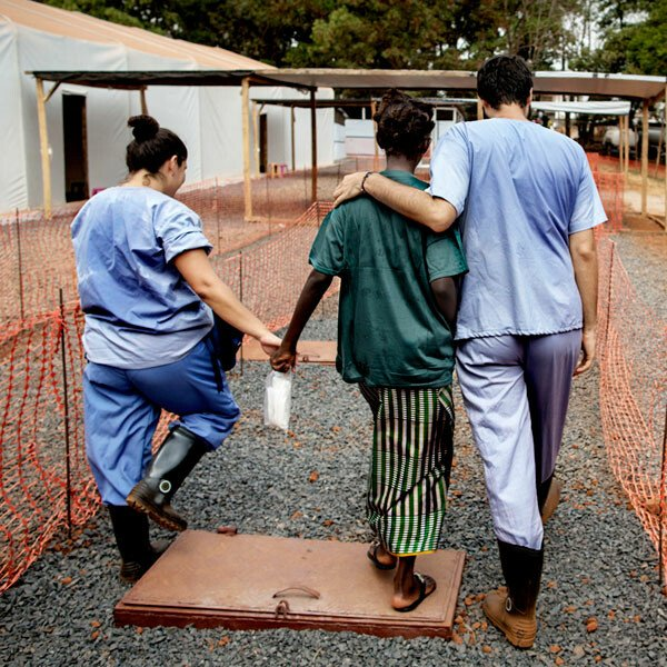 A patient with health workers at an Ebola treatment facility built by Médecins Sans Frontières in Freetown, Sierra Leone.