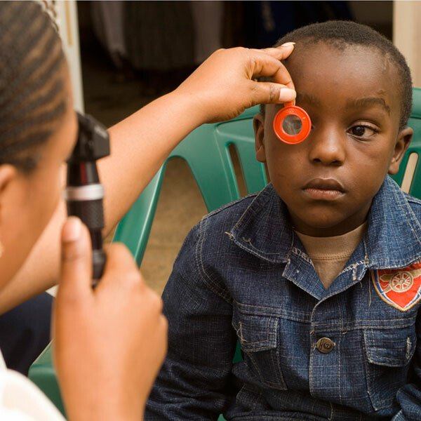 Doctor examining a young boy's eyes at a community ophthalmology centre