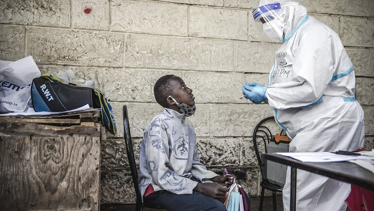 A kid selling face masks in the street and a health worker wearing a hazmat suit.
