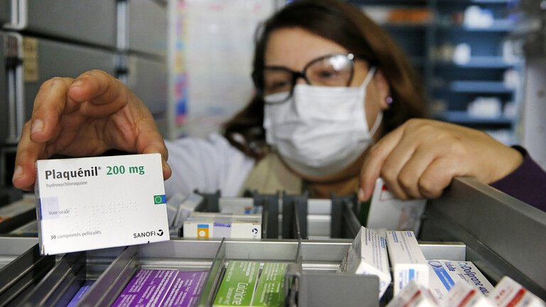 A pharmacy employee wearing a protective mask shows a box of Plaquenil (Chloroquine).