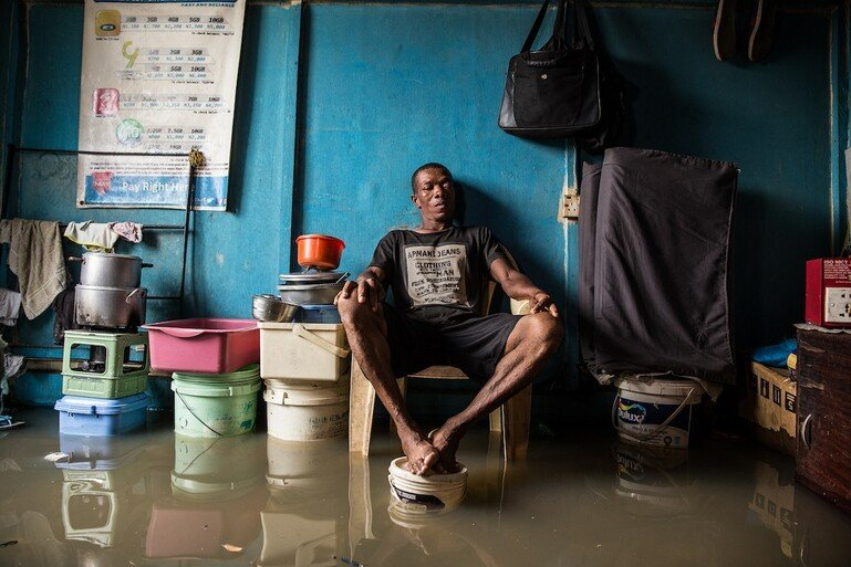 A man sits in his room with his feet up on a paint bucket to avoid floodwater.