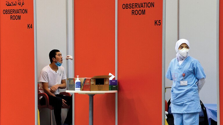 A nurse wearing a face mask and a vaccine trial volunteer sitting in an observation room in a repurposed convention centre in Manama, Bahrain.