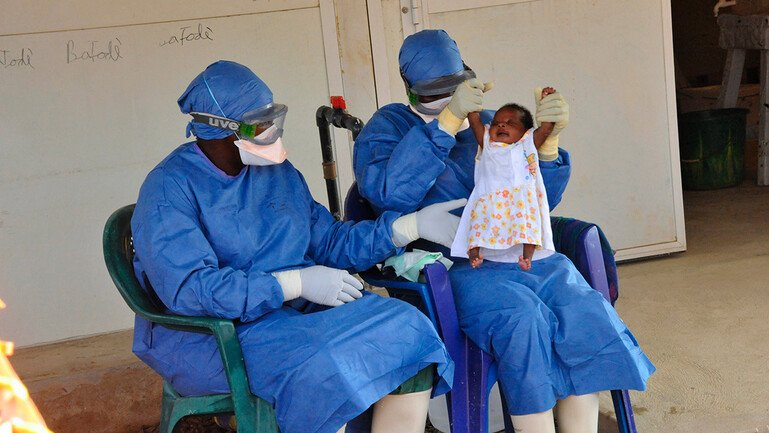 Two medical workers hold up baby Noubia, the last known patient to contract Ebola in Guinea