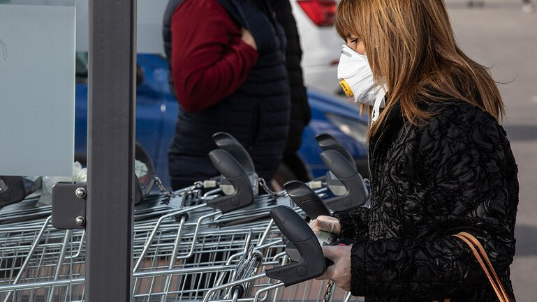 Woman wears face mask and pushes shopping trolley