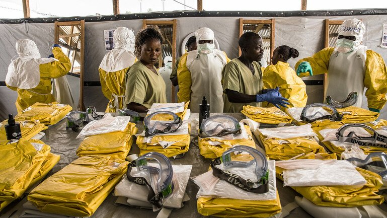 Healthcare workers put their personal protective equipment on before entering the zone with people suspected of having Ebola.