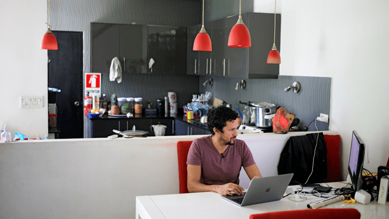 Male researcher sits at desk in his kitchen and looks at laptop