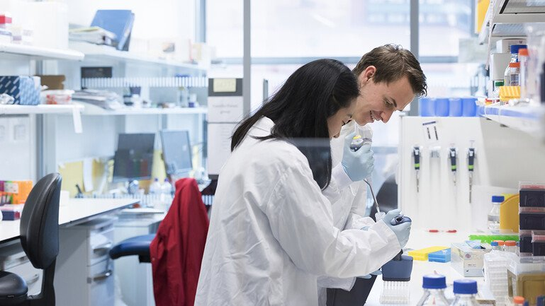 Two researchers carry out an experiment at a lab bench