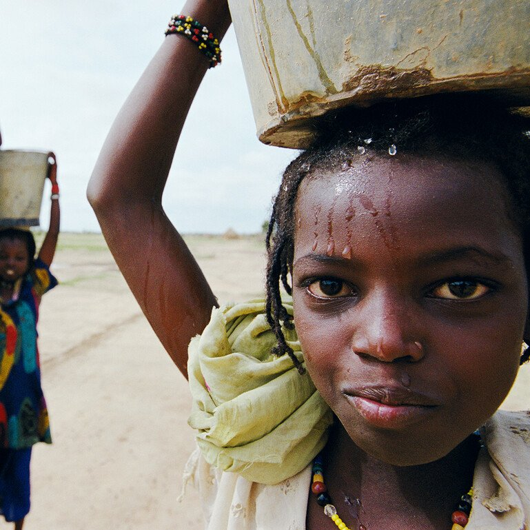A child carrying a pail of water.