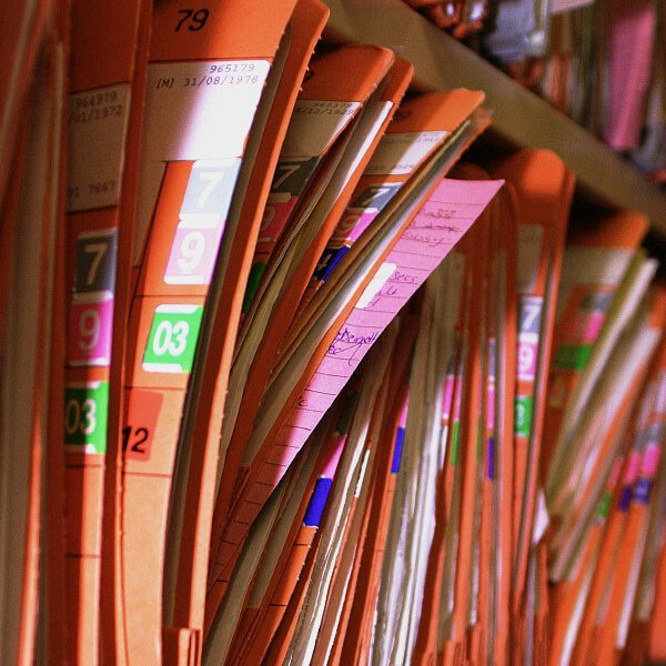 Shelves tightly packed with patients' hospital records in labelled folders