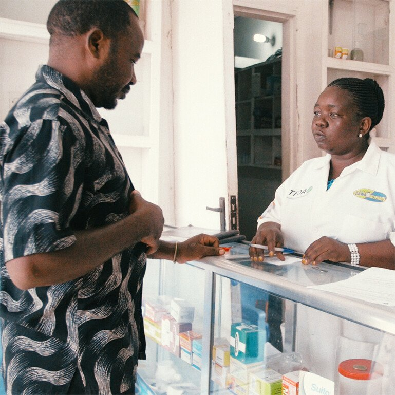 Customer and dispenser in a chemist's shop in Tanzania.