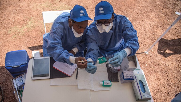 Two nurses prepare to administer vaccines.