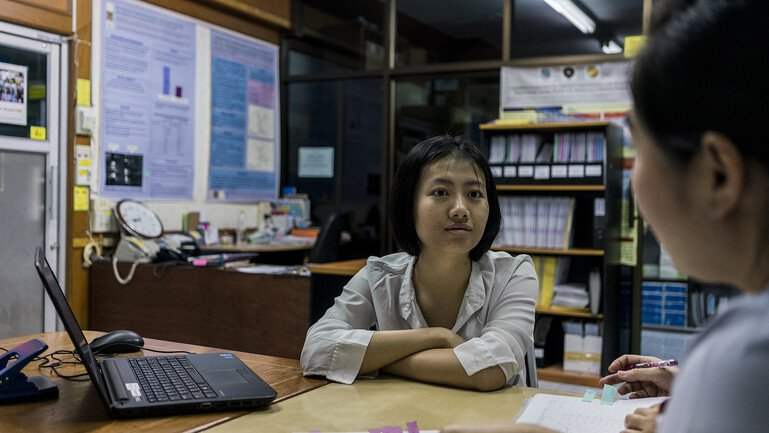 Cherry Lim sitting at a desk, talking to nurses