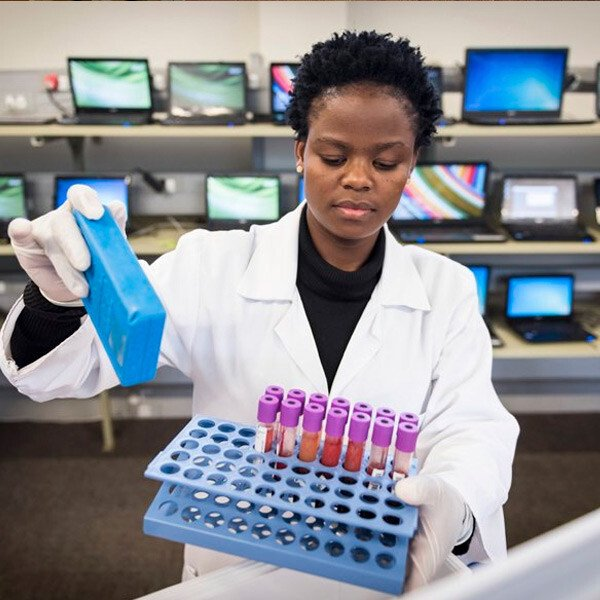 A woman holding a rack of blood samples