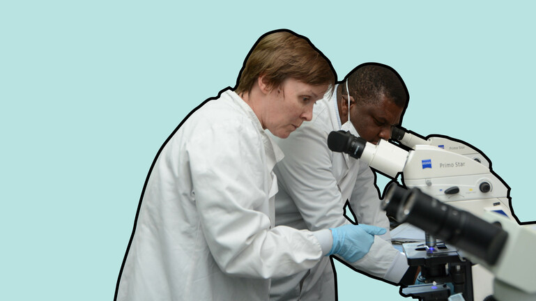 Two researchers look into microscope