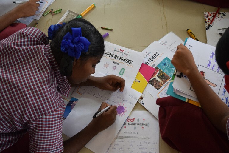 Indian schoolchildren creating comics with paper and pens.