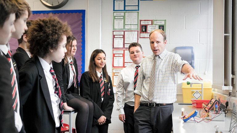 Seven students watch teacher carrying out an experiment