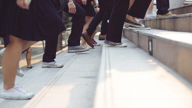Legs of people walking up stairs
