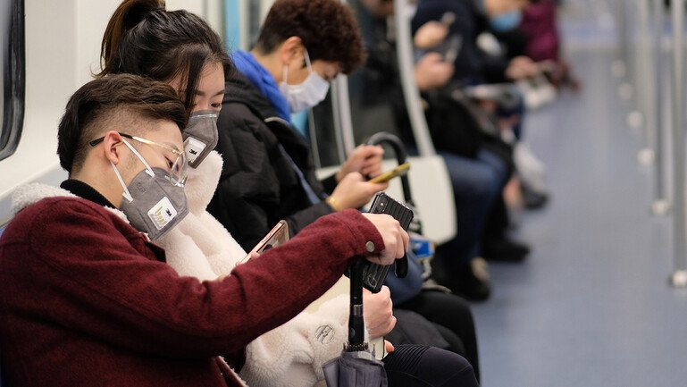 People wearing surgical masks sitting in subway in Shanghai, China.
