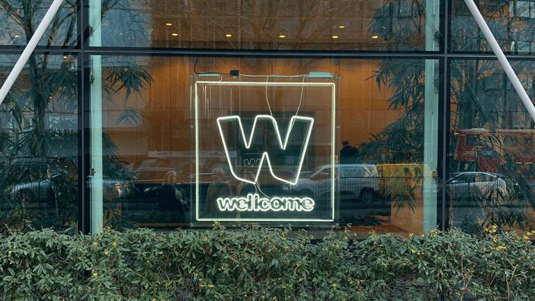 Neon Wellcome logo in window