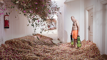 A man holding two flippers stands in a hotel room overgrown with rose bushes